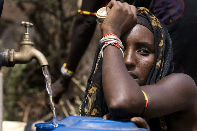 A Gabbra woman looks on as the water fills his can