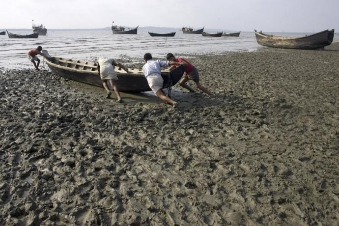 Fishermen push a boat in the sea, Kuruskul Village, Cox's Bazar - © Giulio Napolitano