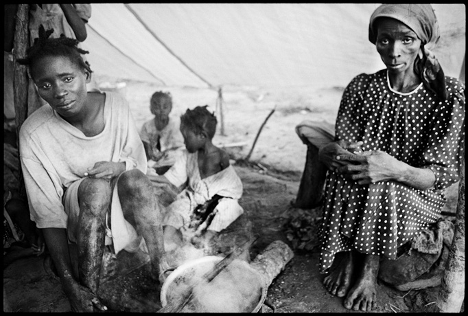 Muatchimbo, Moxico Region, Internally Displaced People inside their tents boiling greens - © Giulio Napolitano